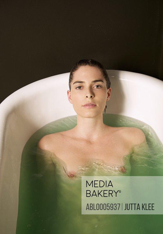 Portrait of a nude woman taking a bath