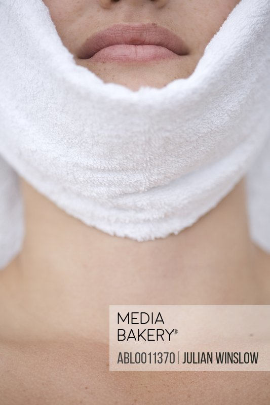Close up of young woman having facial with towel covering chin