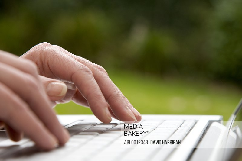 Close up of a woman hands typing on a laptop computer keyboard