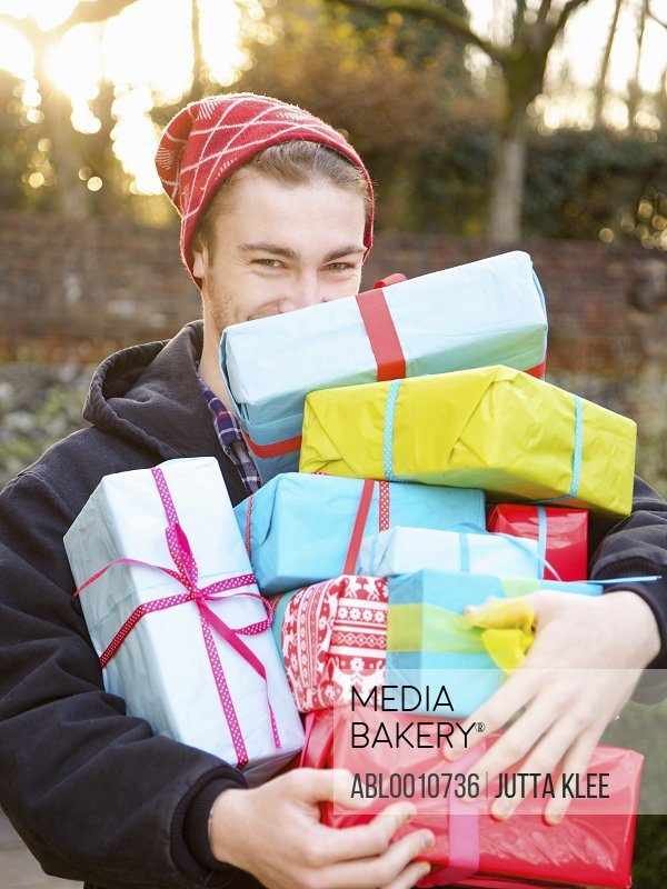 Young Man Holding Stack of Christmas Presents Outdoors