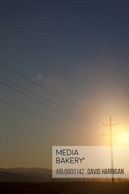 Electric Poles and Wind Turbines at Sunrise