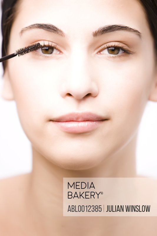 Close up of a young woman applying mascara