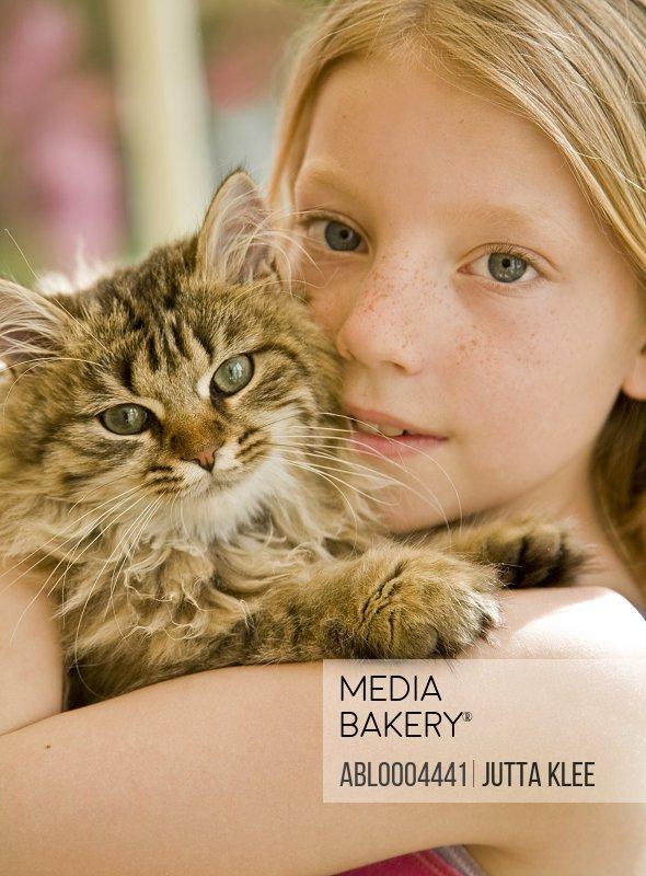 Close up of girl hugging kitten