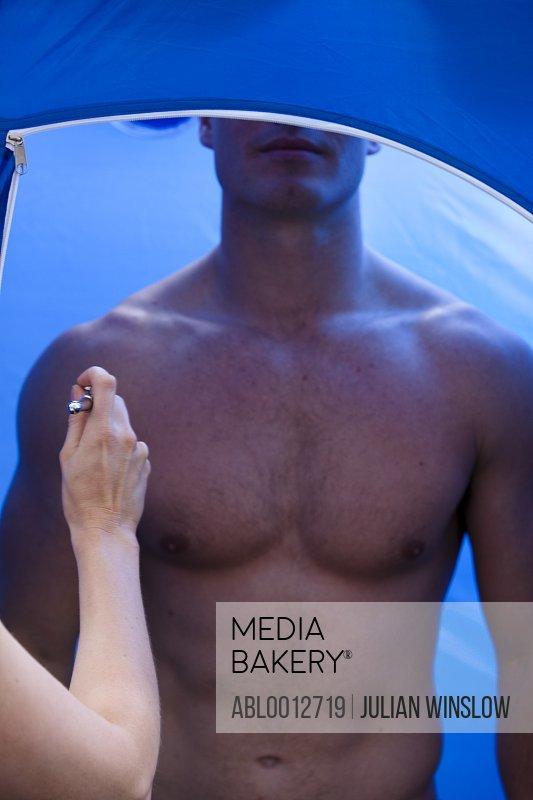 Man getting a fake tan with an airbrush gun