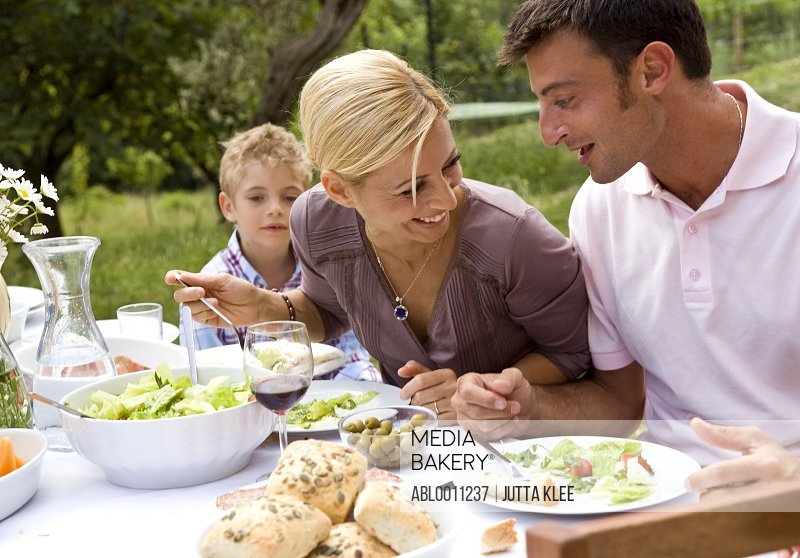 Couple and young boy having lunch outside