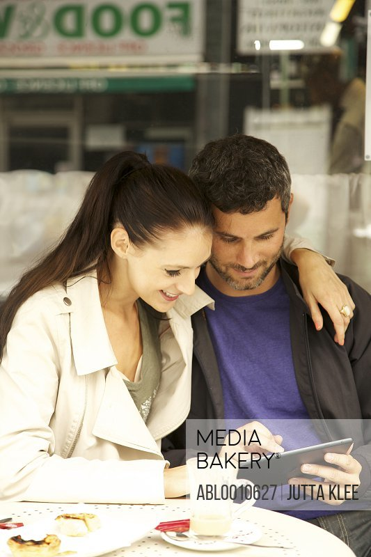 Couple at Outdoor Cafe Using Digital Tablet