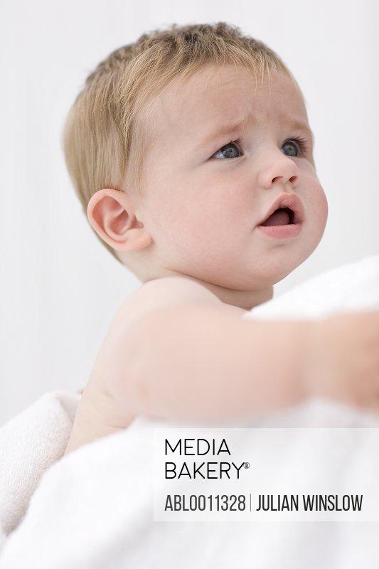 Baby boy leaning against adult shoulder