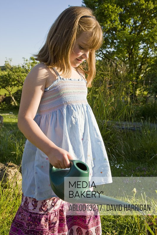 Young Girl Watering Flowers with Watering Can