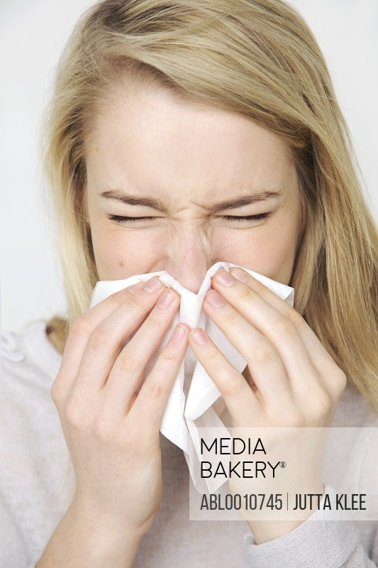 Young Woman Blowing her Nose Sneezing