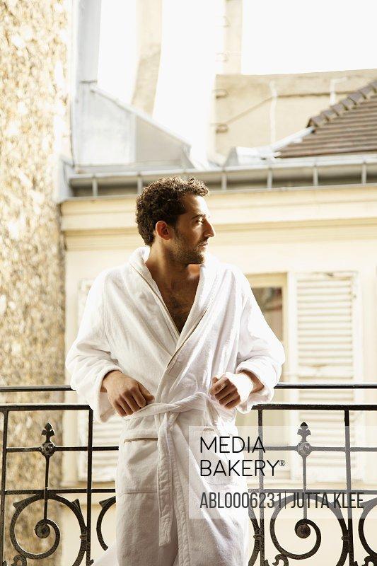 Man in bathrobe leaning on a balcony