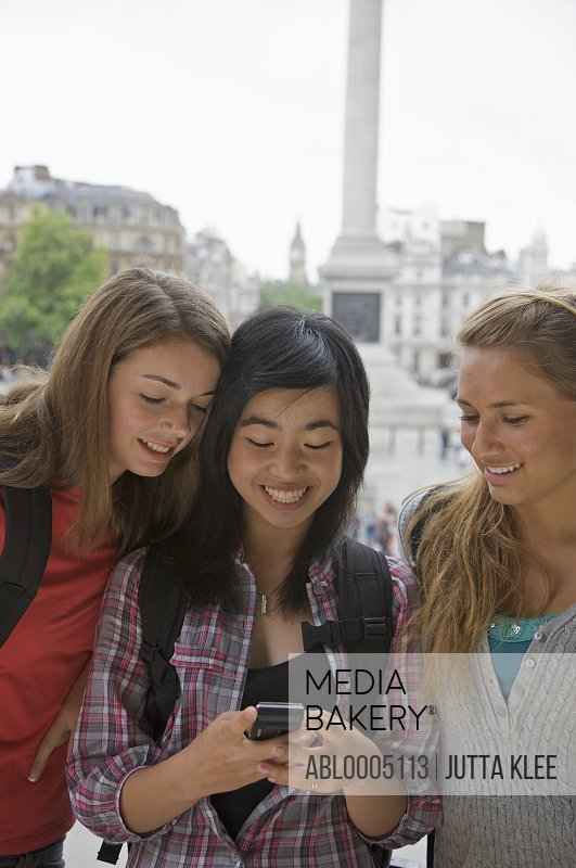 Three smiling teenaged girls using a cell phone in London Trafalgar Square