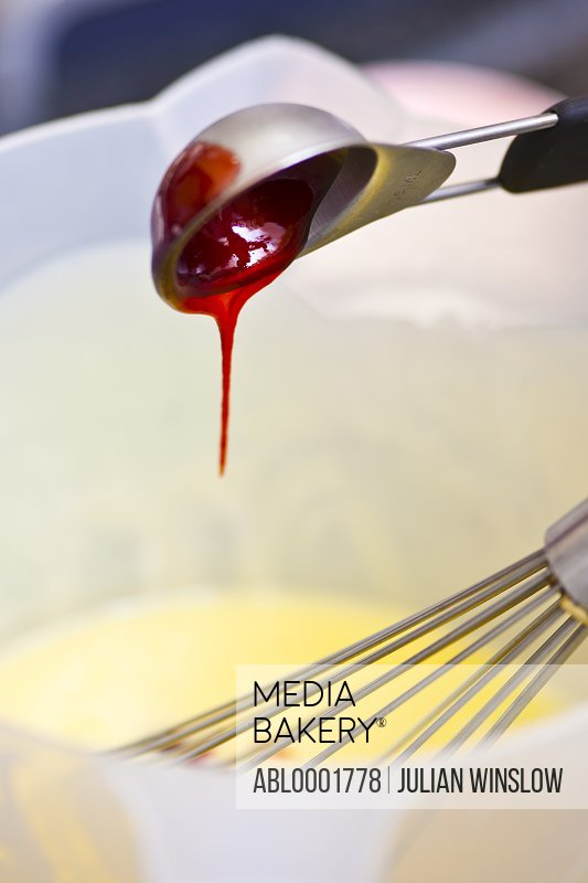Close up of a whisk and a spoon dripping red coulis