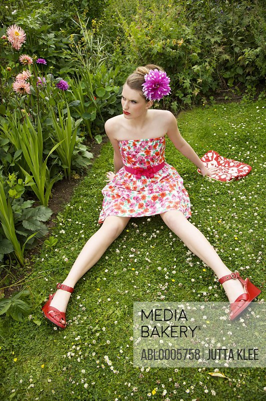Young woman sitting  on the grass in a flower garden