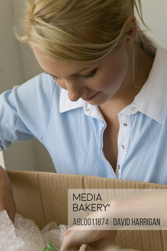 Close up of a young woman looking in a cardboard box