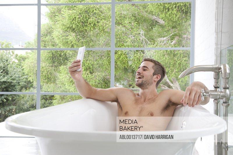 Smiling Man in Bathtub Taking Selfie
