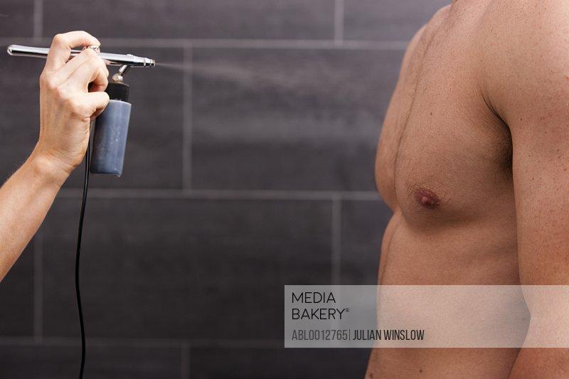 Profile of a man getting a fake tan with an airbrush gun
