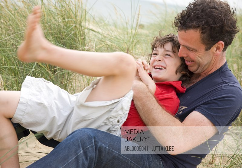 Father and son sitting on a beach smiling and fighting