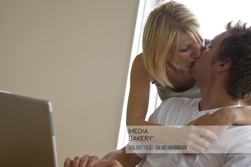 Couple sitting in front of laptop kissing