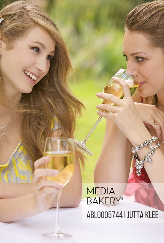 Close up of two young women drinking wine