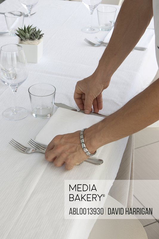 Close up of Waiter's Hands Arranging Cutlery on Restaurant Table