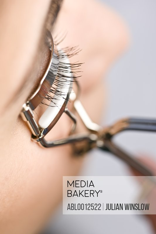 Profile of woman using an eyelash curler - extreme close up