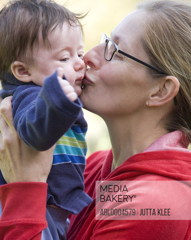 Close up of a woman kissing a little boy