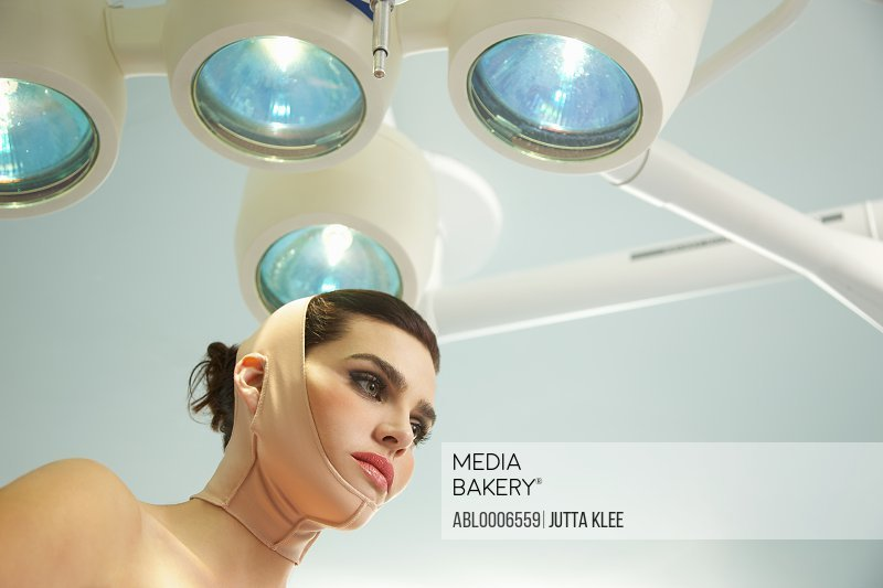 Woman with Elastic Bandage on Face and Neck under Surgical Lamp - Low angle view