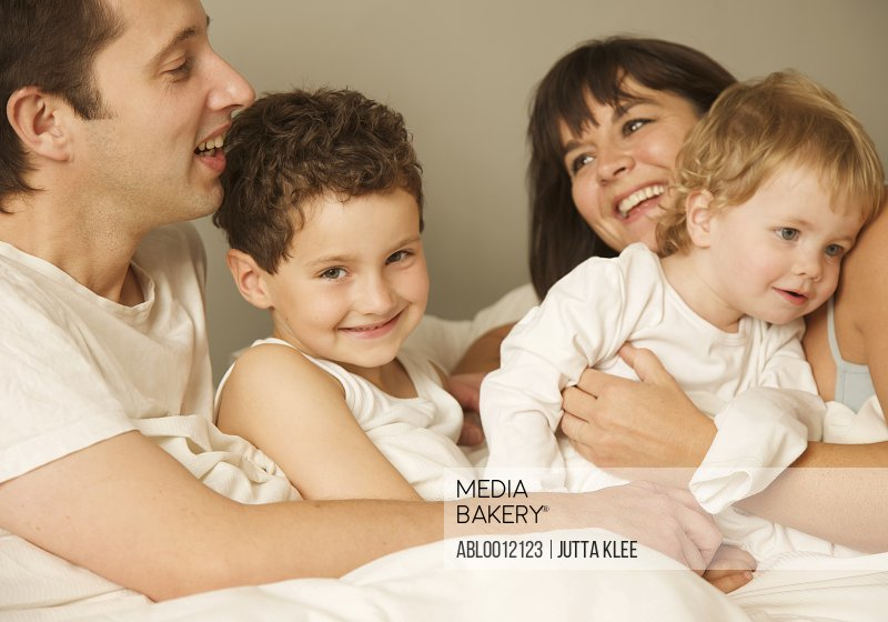 Family in bed hugging and smiling