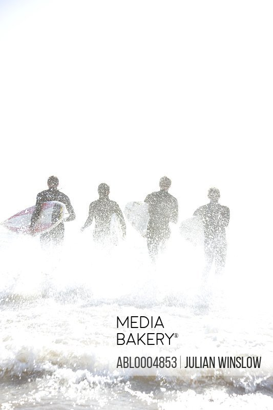 Back view of surfers running in the sea holding surfboards