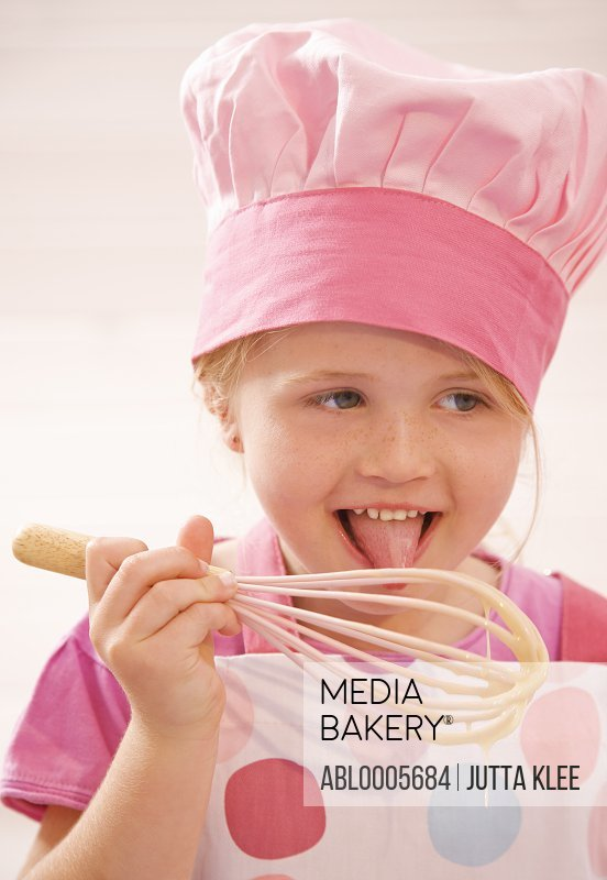 Young girl licking cake mix from a whisk