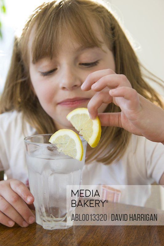 Girl Playing with Slice of Lemon over a Glass of Water