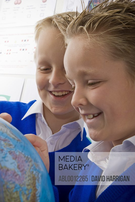 Two smiling boys inspecting a world globe