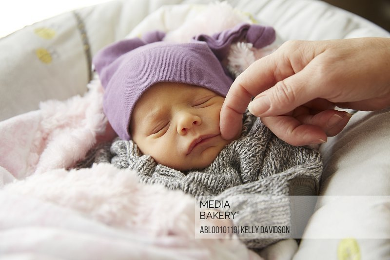 Woman's Hand Caressing Baby Girl Face