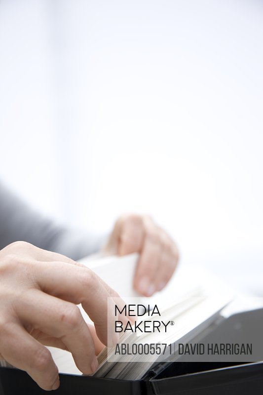 Close up of a woman hands flicking through contact cards