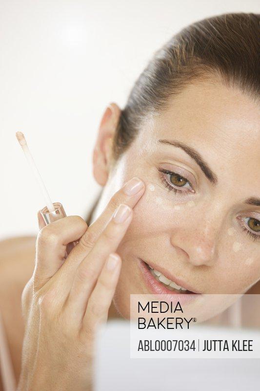 Woman Applying Concealer under Eyes