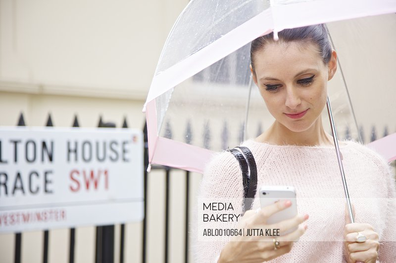 Woman Holding Umbrella in a London Street Using Smartphone