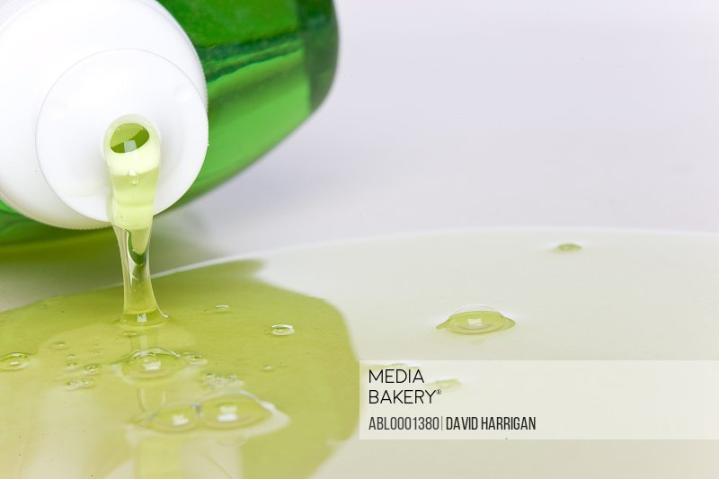 Close up of a plastic bottle with green dishwashing detergent spilling out