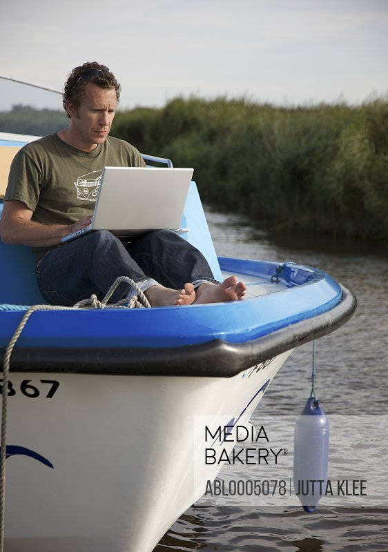 Man sitting on the bow of a boat using a laptop computer