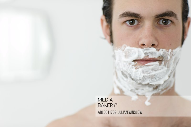 Close up of a young man with shaving cream on his face