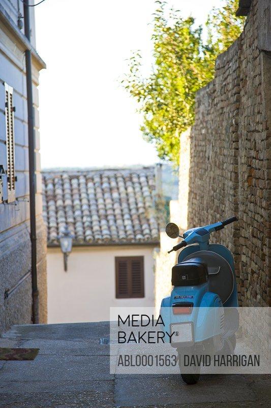 Cyan vespa parked in a street