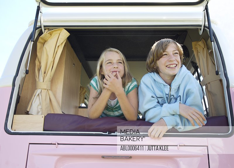 Boy and Girl Looking out of Camper Van Rear Window