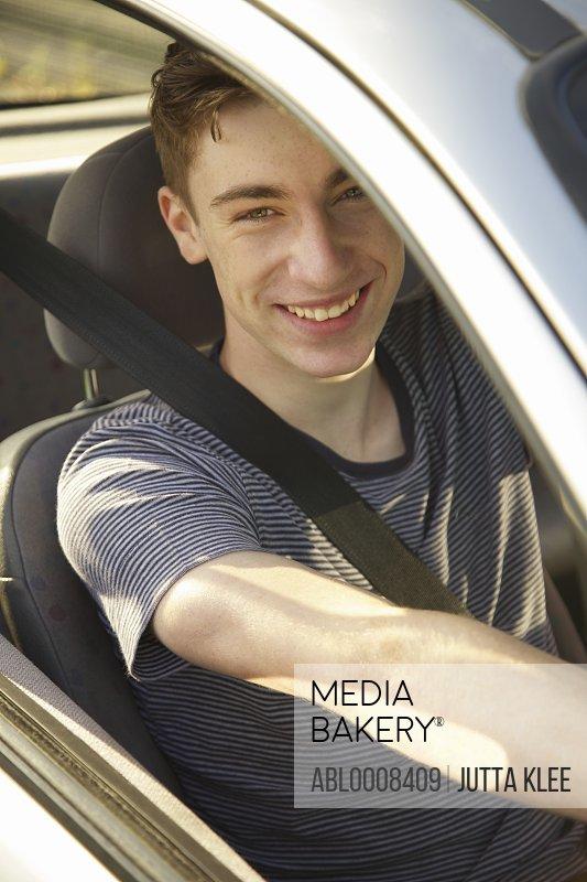 Smiling Teenage Boy Driving Car