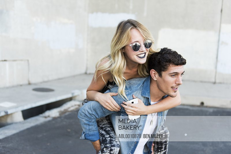 Man Carrying Woman on his back Outdoors