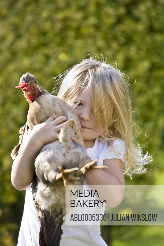 Young girl holding a chicken in her arms
