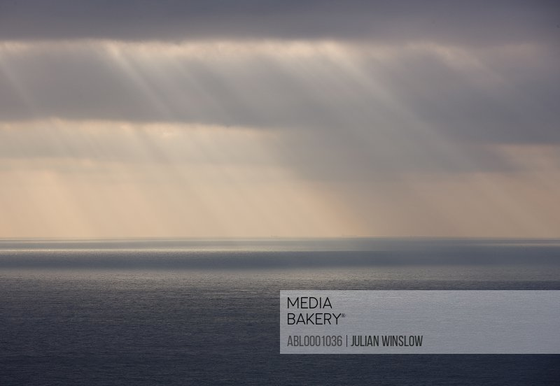 Grey sky with rain and sun rays shining on the ocean