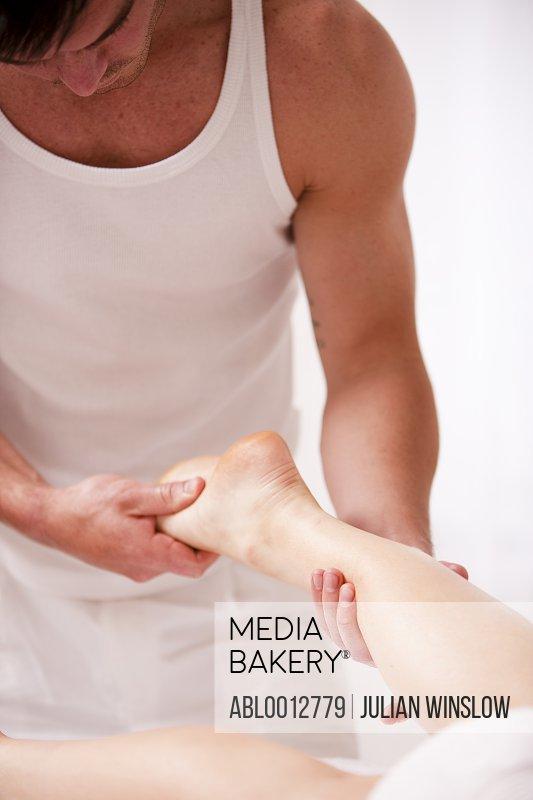 Masseur massaging a woman foot