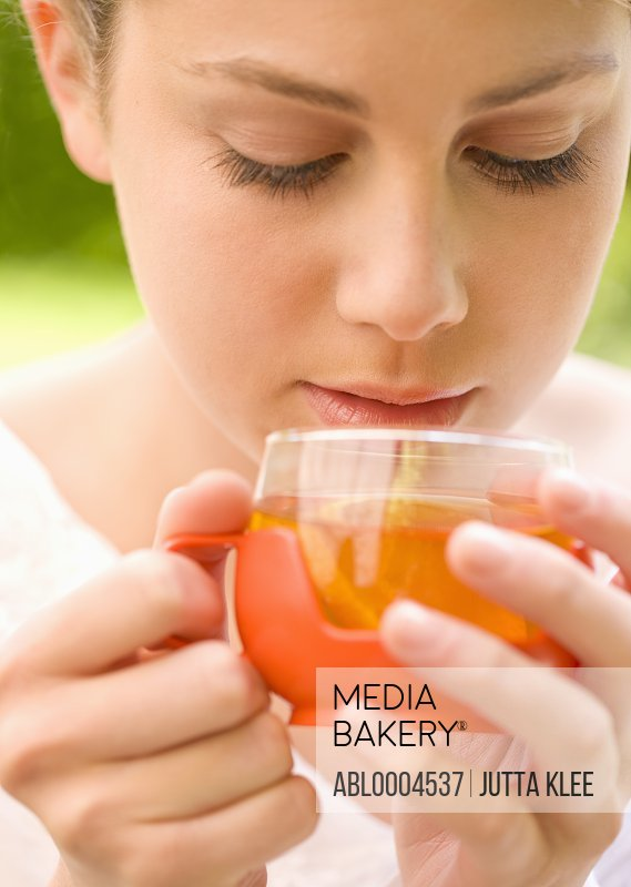Close up of a young woman holding a cup of lemon tea