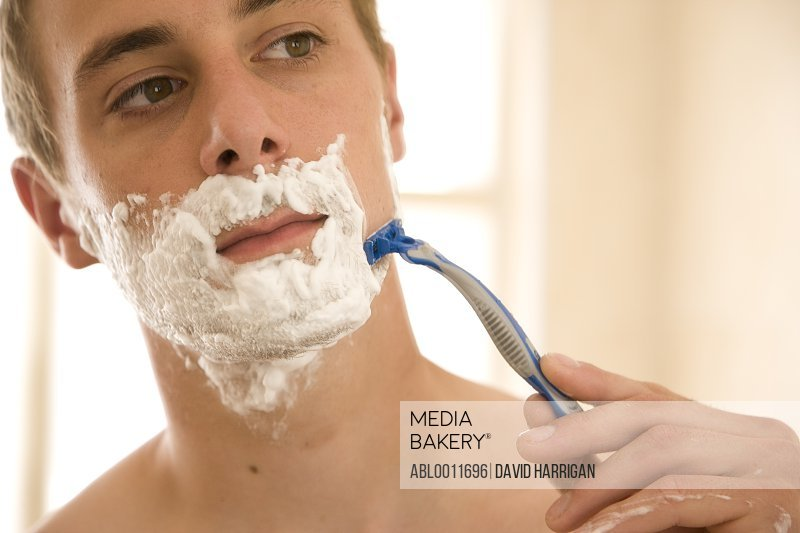 Young man shaving and holding razor<br><br><span style='color: red'>Cannot be used in Beauty Industry in Japan thru September 30, 2021.</span><br><br><br>