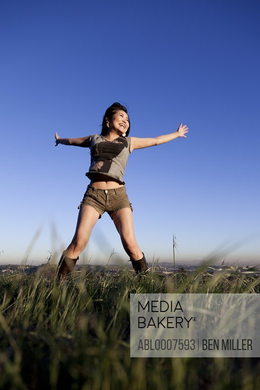 Smiling Young Woman with Arms Outstretched Outdoors