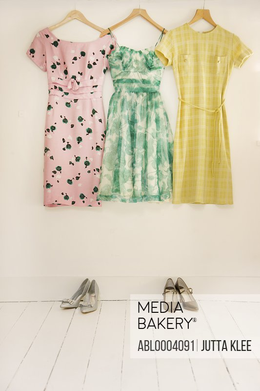 Dresses Hanging against White Wall with Shoes